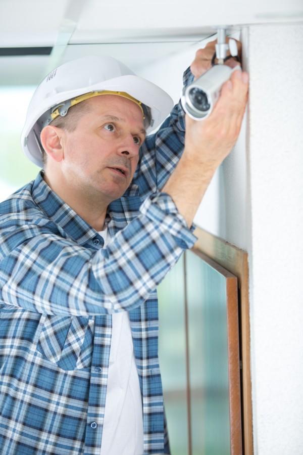 elektryk instaluje kamerę do alarmu lub monitoringu